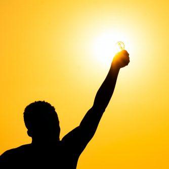 man holding up a lightbulb